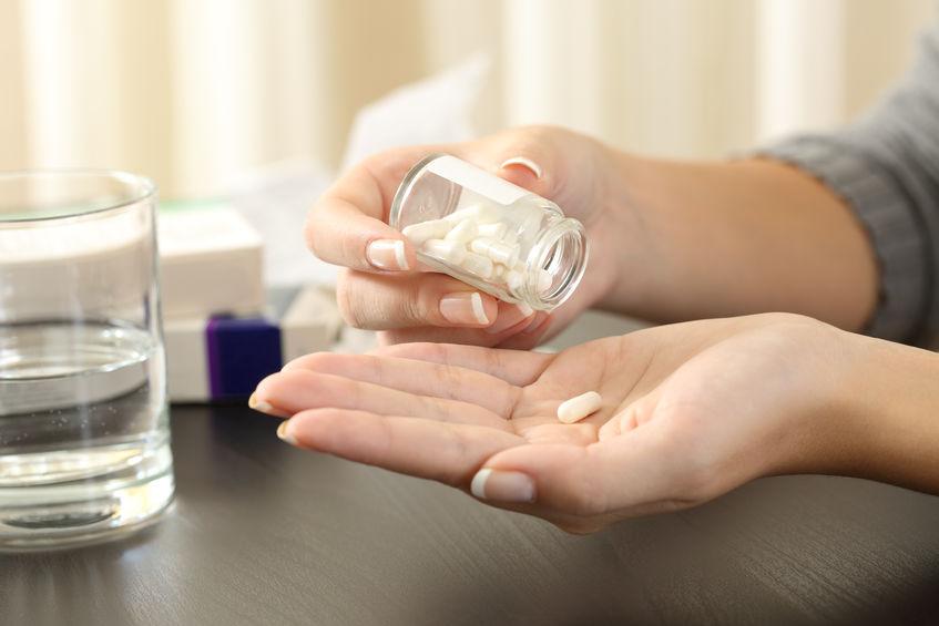 Vrouw die een pil uit de fles