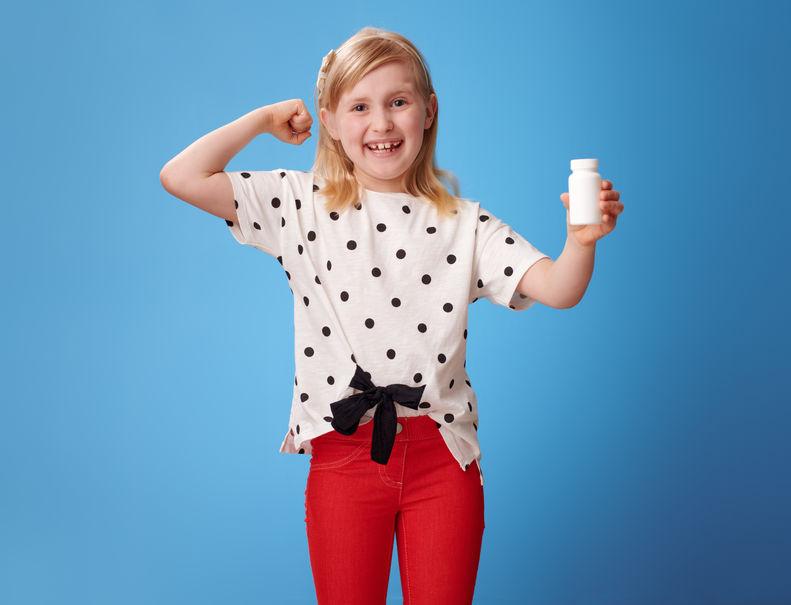 meisje met flessen vitamines en biceps gebaar op blauw