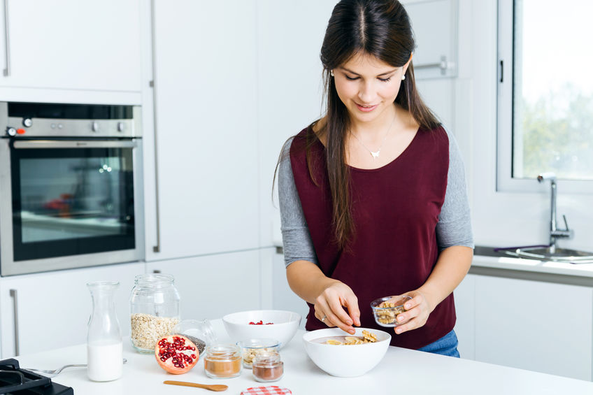 Mooie jonge vrouw die graangewassenkommen in de keuken voorbereidt.
