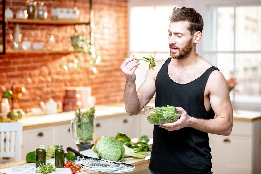 Sport man met gezonde salade thuis