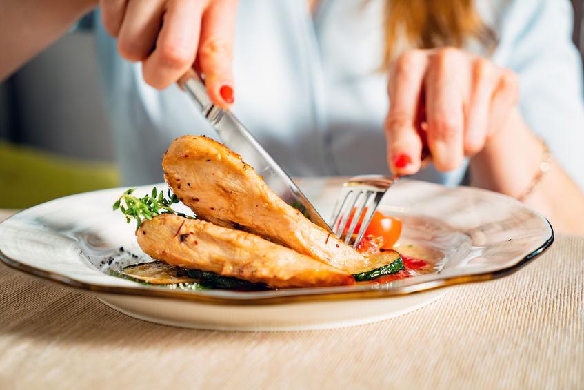 vrouw die gegrilde kippenborst eet