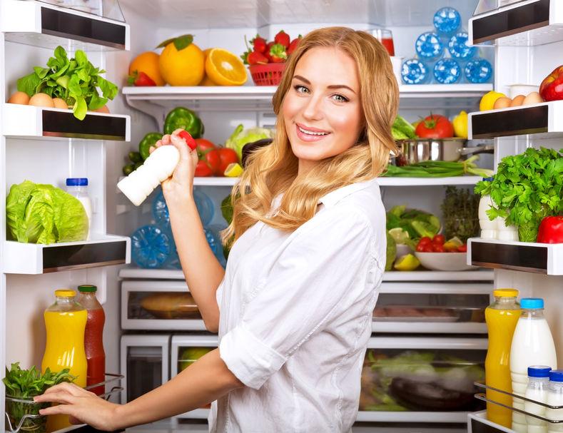 Vrouw koos melk in geopende koelkast