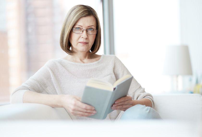 portret van volwassen vrouw met boek camera kijken