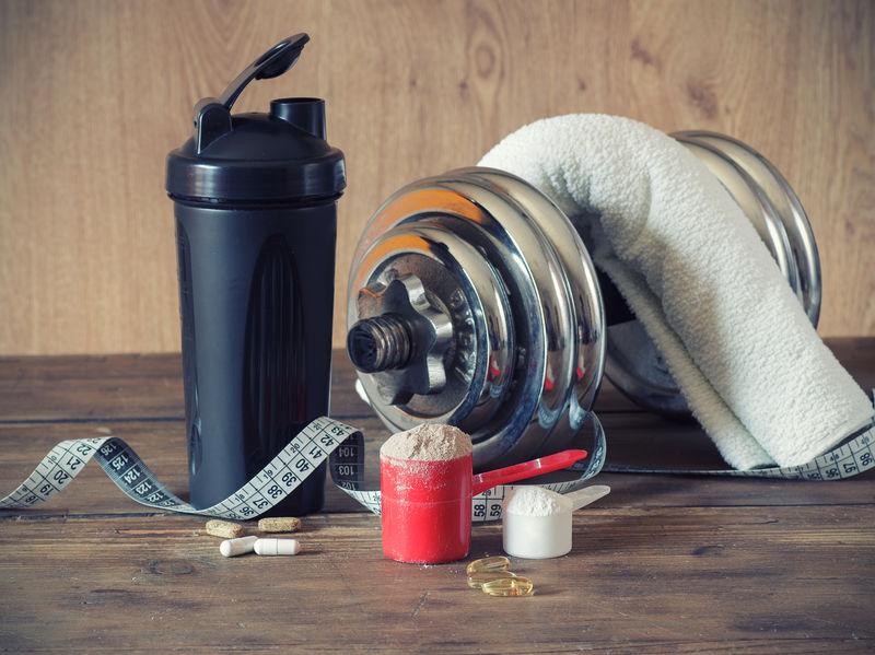 Weiproteïnepoeder in lepel met vitaminen en plastic schudbeker op houten achtergrond