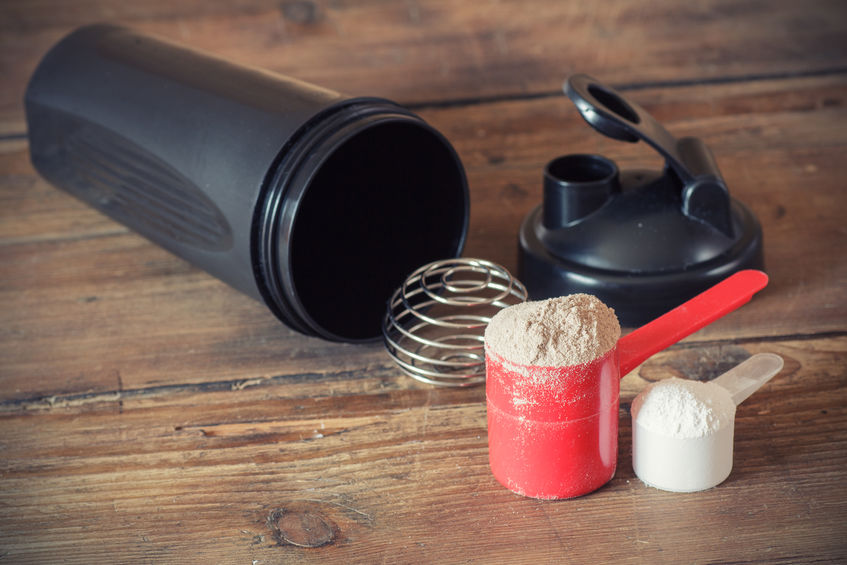 Weiproteïnepoeder in lepel en plastic schudbeker op houten achtergrond