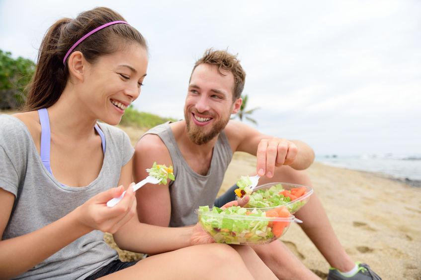 gelukkige jonge mensen die gezonde salade eten voor de lunch.