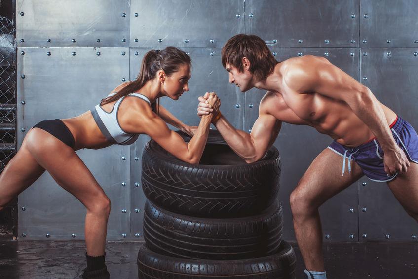 Atleet gespierde sportmannen man en vrouw met handen gevouwen arm worstelen uitdaging tussen een jong koppel Crossfit fitness