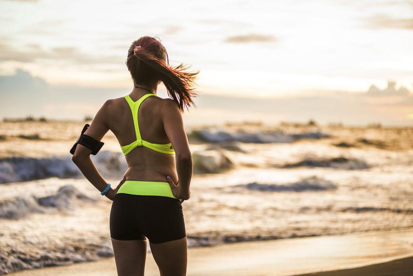 jonge gezonde levensstijlvrouw die bij zonsopgangstrand loopt