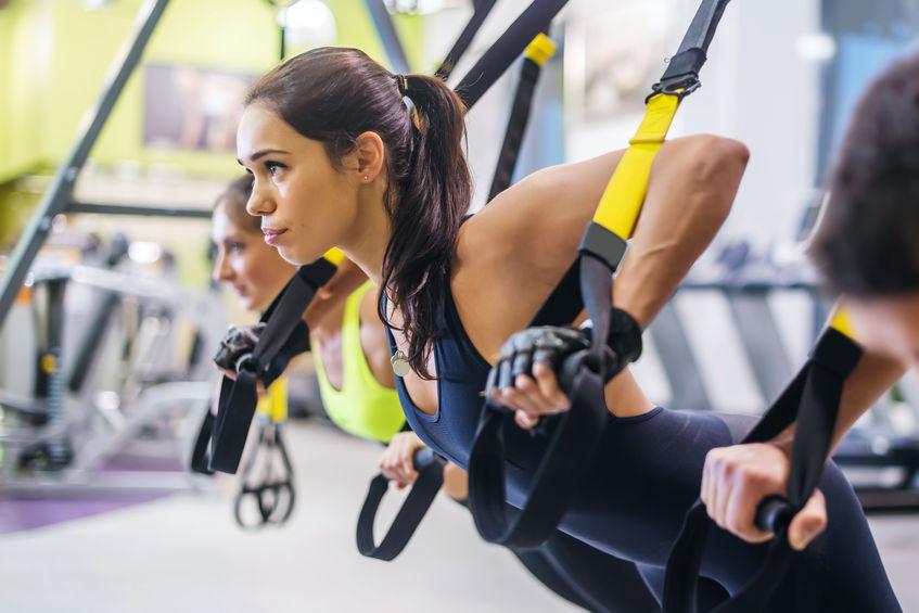 Vrouwen die opdrukoefeningen doen die wapens met trx-