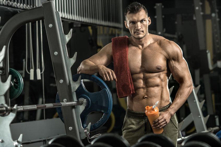 man bodybuilder moe in de sportschool houd shaker met sportieve voeding - eiwit van shaker, verticale foto