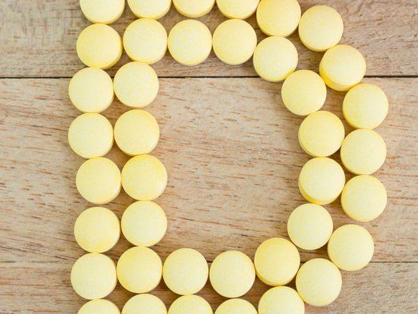 Gele pillen die vorm vormen aan D-alfabet op houten achtergrond