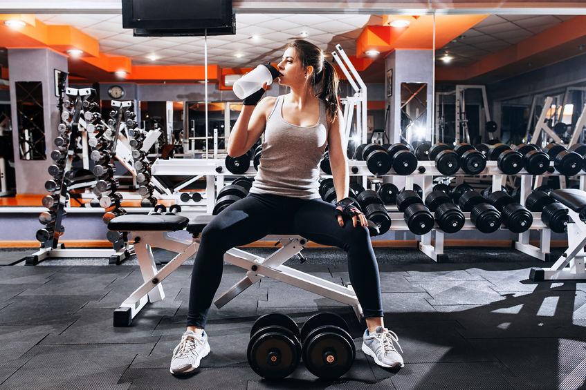 Het bodybuildermeisje ontspant na uitputtende opleiding