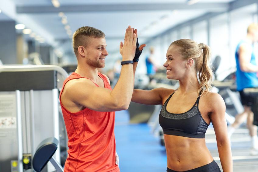 glimlachende man en vrouw die high five in gymnastiek doen