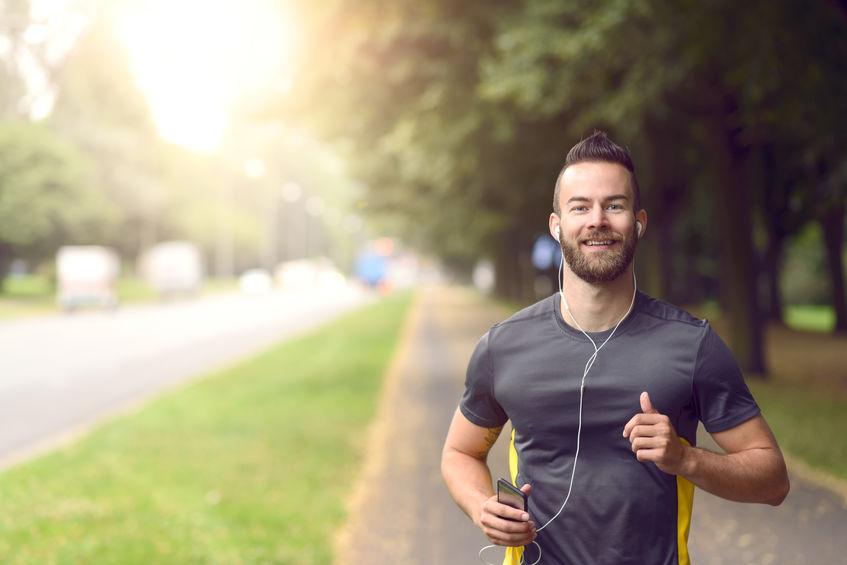 Man joggen langs een stoep op een drukke weg