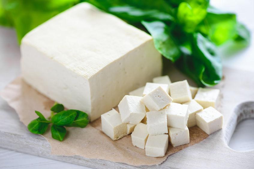 sojakaas tofu in blokjes gesneden op een snijplank, basilicum close-up