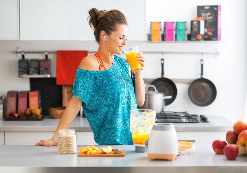 Gelukkige geschiktheids jonge vrouw het drinken pompoen smoothie in keuken
