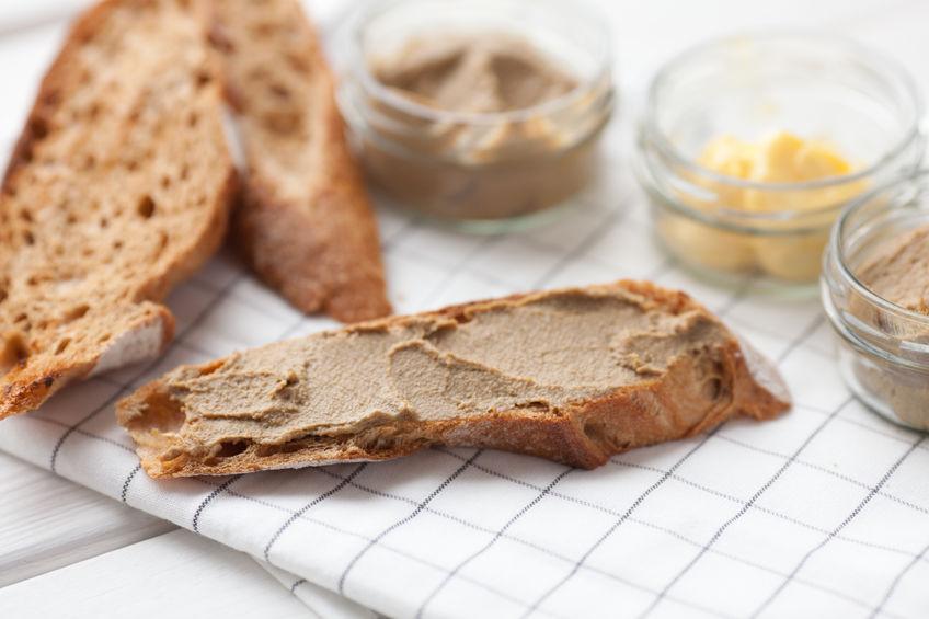 Brood met kalfsvlees en konijnenpastei met boter op een textielachtergrond. Bovenaanzicht
