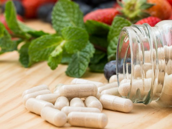 Vitaminensupplementen in fles op houten lijst.