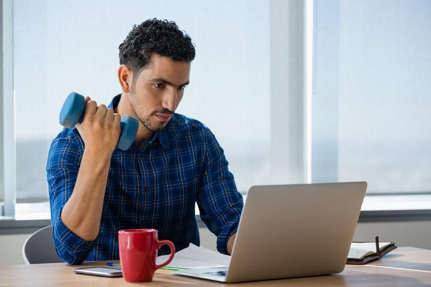Uitvoerend oefenen met halters tijdens het gebruik van de laptop