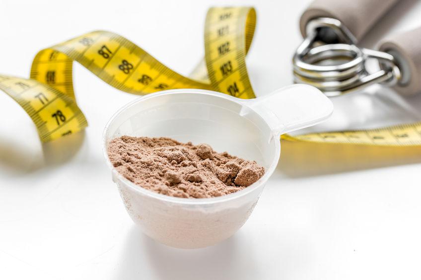 eiwitpoeder voor fitnessvoeding om te beginnen met trainen en tape witte achtergrond te meten