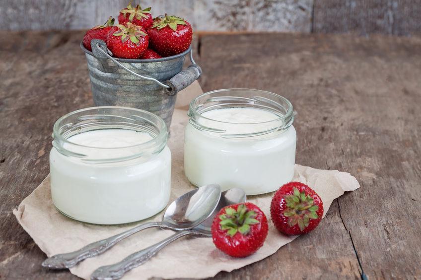 yoghurt in een glas en een emmer met verse aardbeien op een woo