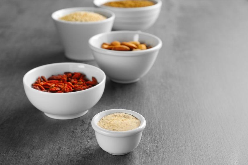 Samenstelling met assortiment van superfood producten in kommen op grijze tafel