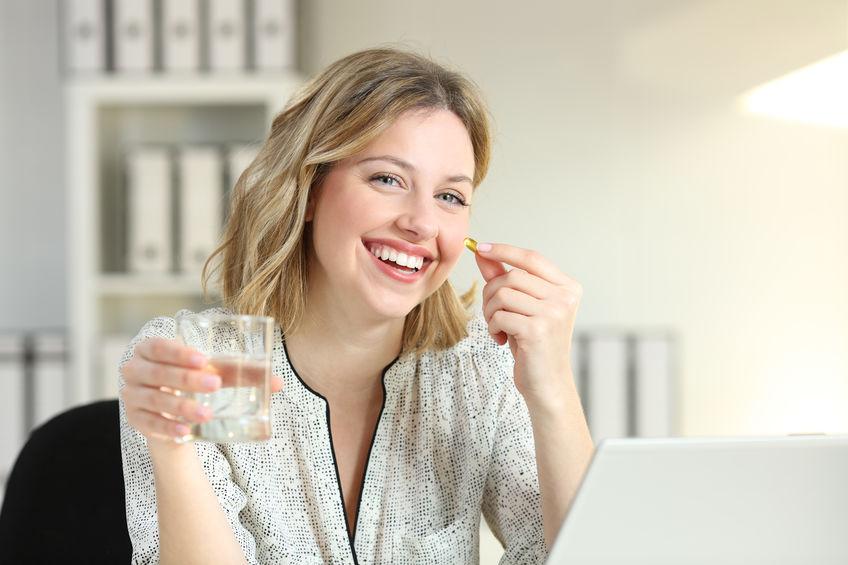 Gelukkige beambte die een pil van het vitaminesupplement toont