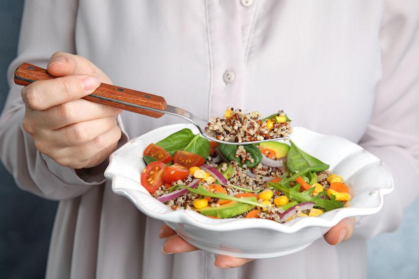 Vrouw die gezonde quinoasalade met groenten van plaat eet, close-up