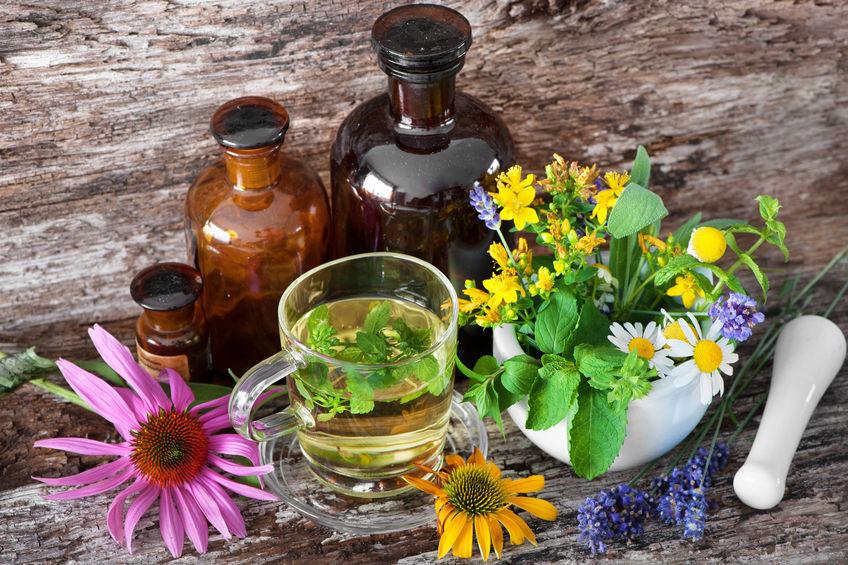 Kopje kruidenthee met geneeskrachtige flessen en geneeskrachtige kruiden in ma