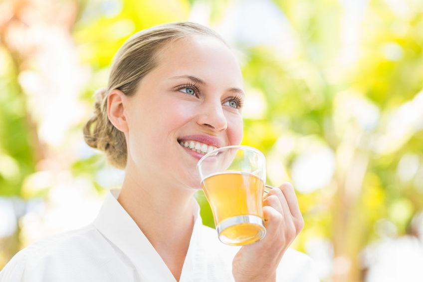 Aantrekkelijke vrouw het drinken van thee in een glas op kuuroordcentrum