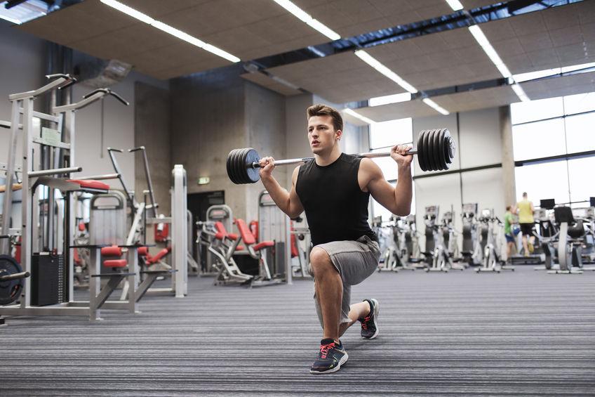 de spieren van de jonge mensenverbuiging met barbell in gymnastiek