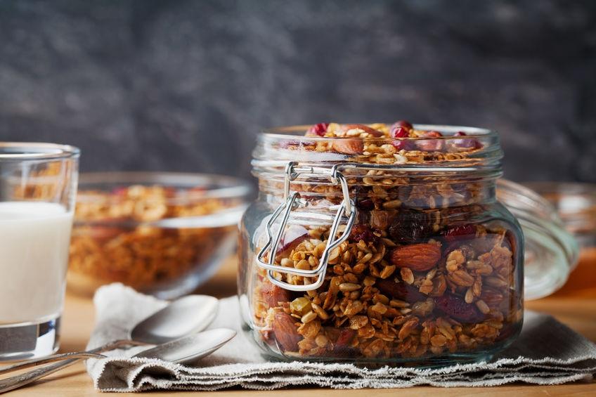 Zelfgemaakte muesli in pot op rustieke tafel, gezond ontbijt van havermout muesli, noten, zaden en gedroogd fruit