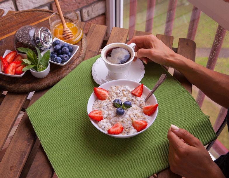 De geschiktheidsvrouw heeft een gezond ontbijt. Gezonde zelfgemaakte havermout met bessen