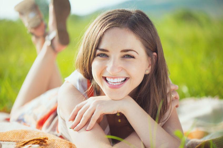 Portret van een mooie jonge lachende vrouw op gras