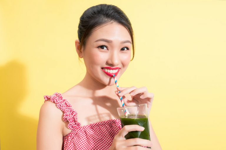 Aziatische eigenschappenmeisje met groen sap