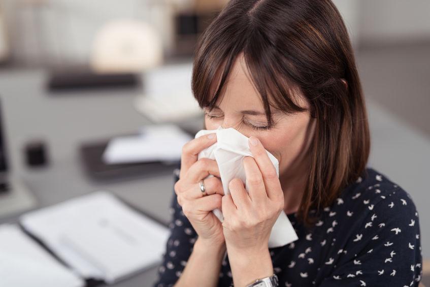 Zieke jonge kantoorvrouw niest in een weefsel