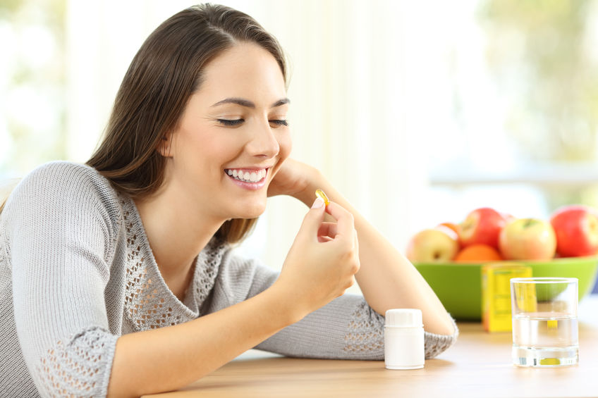 Vrouw die omega 3 vitaminepillen neemt