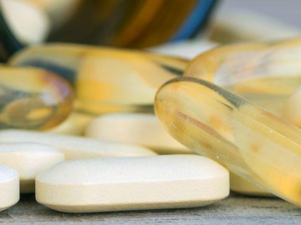 Pillen of vitamine in geneeskundeflessen op hout achtergrond