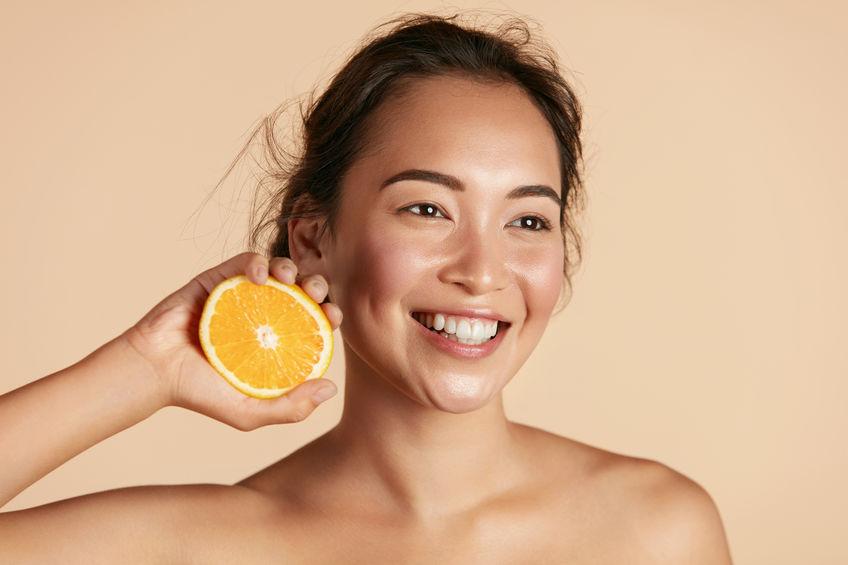 meisje glimlachend en met een sinaasappel